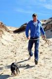 Hombre y perro en dunas de arena Fotografía de archivo