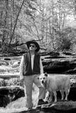 Hombre y perro en el BW del río Imagenes de archivo