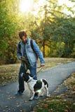 Hombre y perro en parque del otoño imagenes de archivo