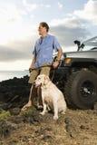 Hombre y perro por SUV en la playa Fotos de archivo libres de regalías