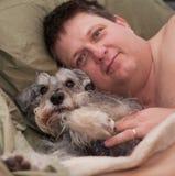 Hombre y perro que se relajan Foto de archivo