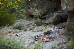 Hombre y perro Schnauzer miniatura cerca del barranco Enjoing el tiempo afuera Árboles y montañas verdes en el fondo fotos de archivo