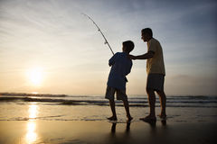 Hombre y pesca joven del muchacho en resaca Foto de archivo
