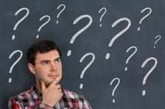 Hombre y pizarra pensativos con los signos de interrogación Imagenes de archivo