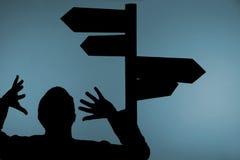Hombre y poste indicador confusos Imagen de archivo