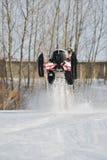 Hombre y salto rápido de la moto de nieve de la acción Imágenes de archivo libres de regalías