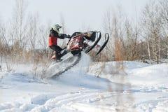 Hombre y salto rápido de la moto de nieve de la acción Imagen de archivo