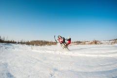 Hombre y salto rápido de la moto de nieve de la acción Imagenes de archivo