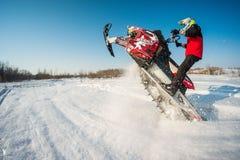 Hombre y salto rápido de la moto de nieve de la acción Foto de archivo
