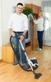 Hombre y su esposa que limpian en casa Imagenes de archivo
