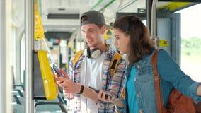 Hombre y turista de las mujeres que usa boletos de la compra del teléfono en transporte público metrajes
