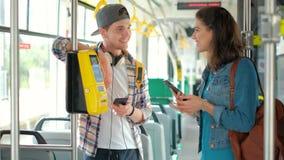Hombre y turista de las mujeres que usa boletos de la compra del teléfono en transporte público almacen de video