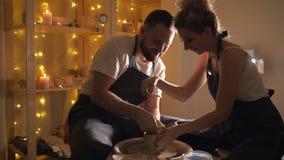 Hombre y una mujer que hace el jarro de la arcilla en la rueda de alfarero metrajes