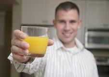 Hombre y zumo de naranja Imagen de archivo