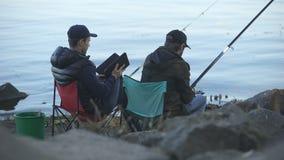 Hombres aburridos que cogen pescados, usando la tableta para buscar tutoriales en la pesca de páginas web almacen de video