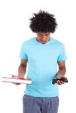 Hombres adolescentes negros jovenes que celebran un libro y un control del videojuego Imagen de archivo libre de regalías
