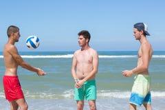 Hombres adolescentes que juegan con la bola en la playa Imagenes de archivo