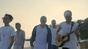 Hombres adultos asiáticos jovenes que caminan en la canción del canto de la playa y tocar la guitarra almacen de metraje de vídeo