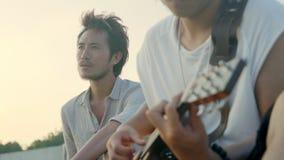 Hombres adultos asiáticos jovenes que cantan tocando la guitarra almacen de video