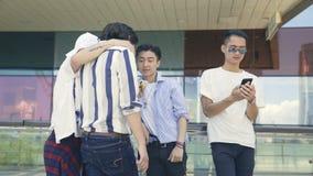 Hombres adultos asiáticos jovenes que cuelgan hacia fuera en la calle que mira el teléfono móvil almacen de video