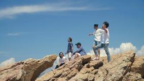 Hombres adultos asiáticos jovenes que defienden encima de rocas el mar metrajes