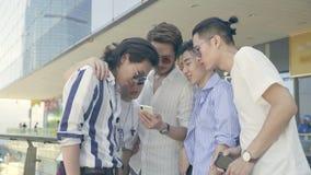 Hombres adultos asiáticos jovenes que miran el teléfono móvil almacen de video