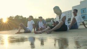Hombres adultos asiáticos jovenes que se sientan en el canto de relajación de la playa tocando la guitarra almacen de metraje de vídeo