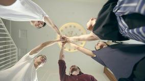 Hombres adultos jovenes asiáticos que ponen las manos juntas para mostrar la determinación y la unidad almacen de video