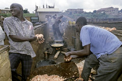 Hombres africanos que calientan la tripa de pescados para engrasar, Kampala Fotos de archivo libres de regalías