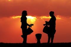 Hombres africanos que juegan el tambor en la puesta del sol Foto de archivo libre de regalías