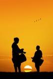 Hombres africanos que juegan el tambor en la puesta del sol Imágenes de archivo libres de regalías