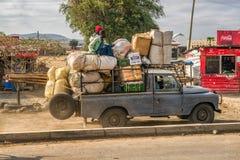 Hombres africanos que transportan mercancías en un coche viejo Imagenes de archivo