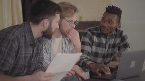 Hombres afroamericanos dos y uno cauc?sico del retrato que descansan junto en casa, sent?ndose delante del ordenador port?til mul metrajes