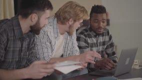 Hombres afroamericanos dos y uno cauc?sico del retrato que descansan junto en casa, sent?ndose delante del ordenador port?til mul almacen de video