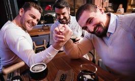 Hombres agradables alegres armwrestling en el pub Foto de archivo