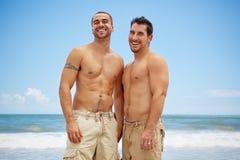 Hombres alegres en la playa Imagenes de archivo