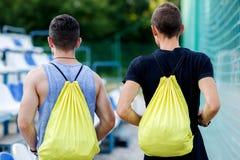 Hombres aptos que van al entrenamiento en la naturaleza con las mochilas Fotografía de archivo libre de regalías