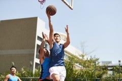 Hombres asiáticos jovenes que juegan a baloncesto fotografía de archivo