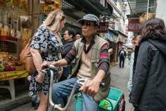 Hombres asiáticos que completan un ciclo en pueblo del Tai O foto de archivo libre de regalías