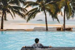 Hombres asiáticos que se relajan en vacaciones de verano de la piscina en la playa fotos de archivo