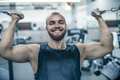 Hombres atléticos fuertes brutales que bombean para arriba el fondo del concepto del levantamiento de pesas del entrenamiento de  foto de archivo libre de regalías
