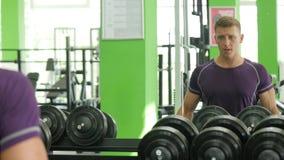 Hombres atléticos fuertes que toman las pesas de gimnasia pesadas para el entrenamiento activo en gimnasio, aptitud metrajes
