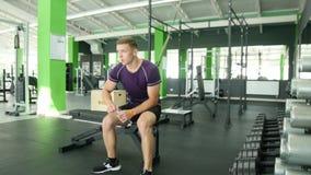 Hombres atléticos fuertes que toman las pesas de gimnasia pesadas para el entrenamiento activo en gimnasio, aptitud almacen de metraje de vídeo