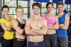 Hombres atléticos y mujeres que presentan los brazos cruzados Imagen de archivo