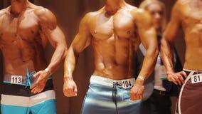 Hombres atractivos con los músculos rasgados que presentan en etapa en la competencia del levantamiento de pesas, deportes metrajes