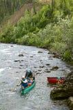 Hombres aventureros en una canoa en rápidos salvajes del río Foto de archivo
