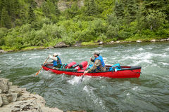 Hombres canoeing en rápidos del río que rabian en Alaska salvaje Foto de archivo libre de regalías