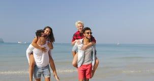 Hombres Carry Women On Back, dos pares caminando en turistas que hablan de la gente alegre feliz de la playa el vacaciones almacen de video
