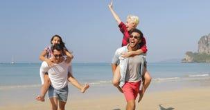 Hombres Carry Women On Back, dos pares que corren en turistas alegres felices de la gente de la playa el vacaciones almacen de video