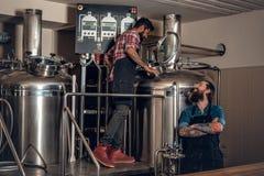 Hombres caucásicos e indios tatuados, barbudos en el microbrewery de la cerveza del arte Imagen de archivo libre de regalías